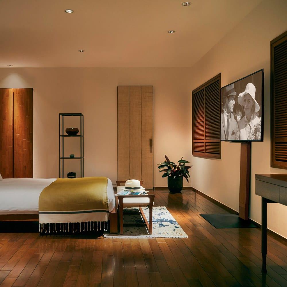 WALL/ウォール 壁寄せテレビスタンド ハイタイプ 大 使用イメージ。寝室でベッドに横たわりながら見やすい高さに設置できます。