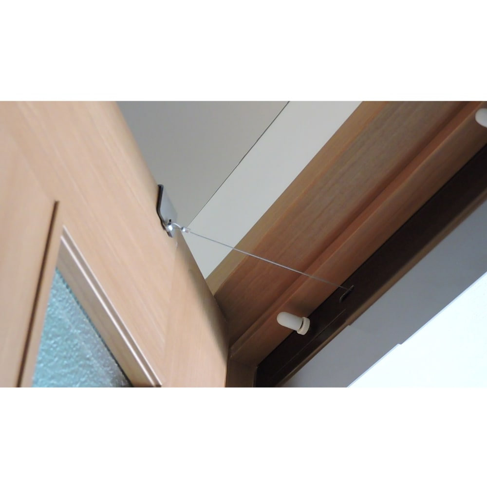 ペット用ドア開閉アイテム「わんにゃんフリーパス」 横から見た図。ワイヤーがドアと商品本体の間に見えています。このワイヤーがドアをひっぱるから開いた後のドアが自動で閉まるのです。