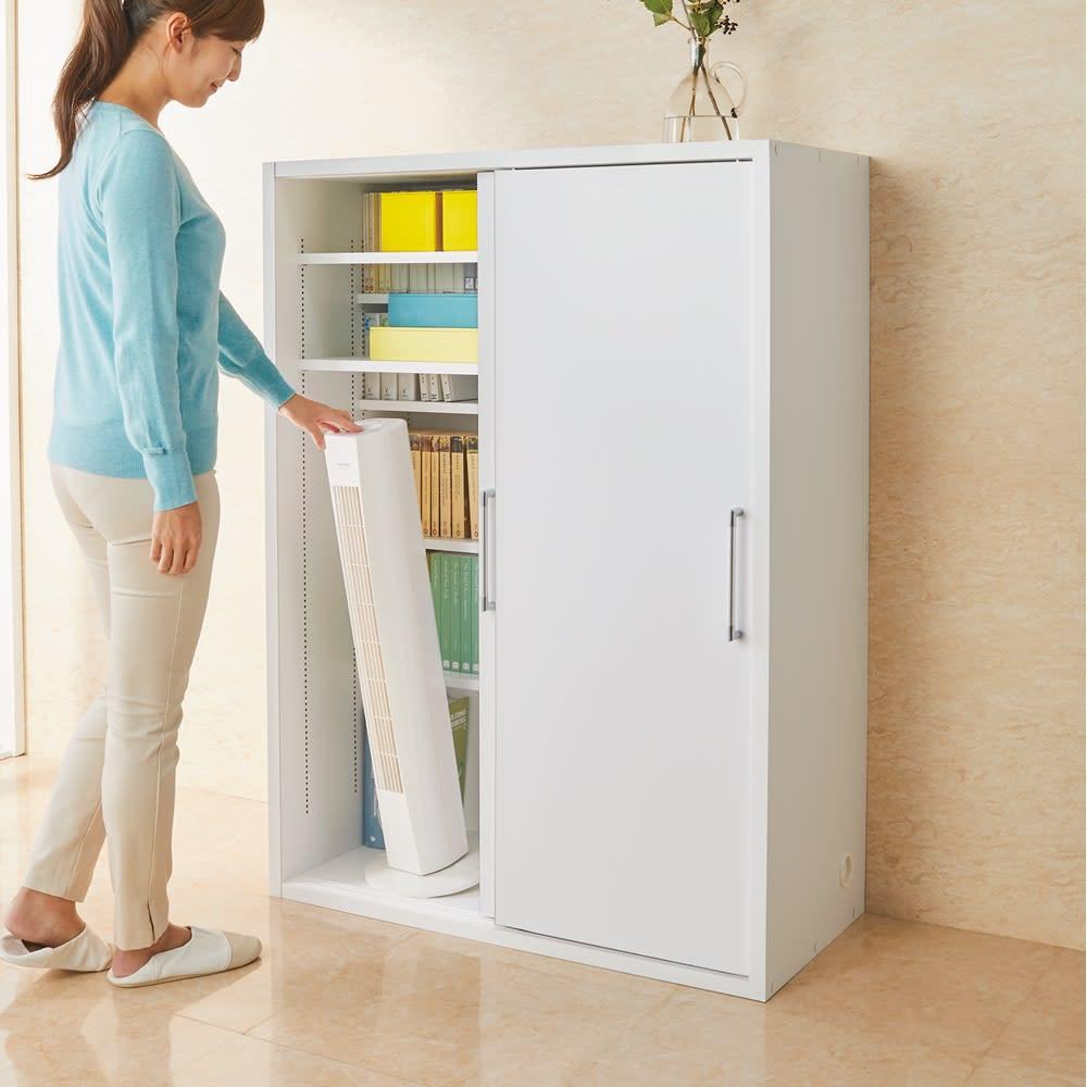 掃除機もしまえる引き戸本棚 ミドルタイプ(幅74高さ125cm) 使用イメージ:(ア)ホワイト ミドルタイプは女性も出し入れしやすいサイズ感。 ※写真は幅90cmタイプです。 モデル身長160cm