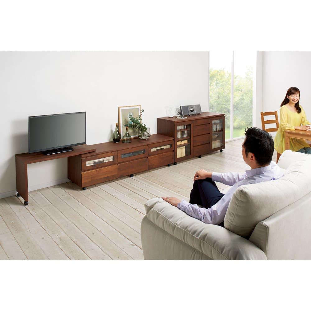 アルダー天然木ユニットボード キャスター付きテレビ台 幅106cm コーディネート例(イ)ダークブラウン リビングから。ネストボード(別売り)は左右どちらにも取り付けられ、幅伸縮や角度調整が自在に。