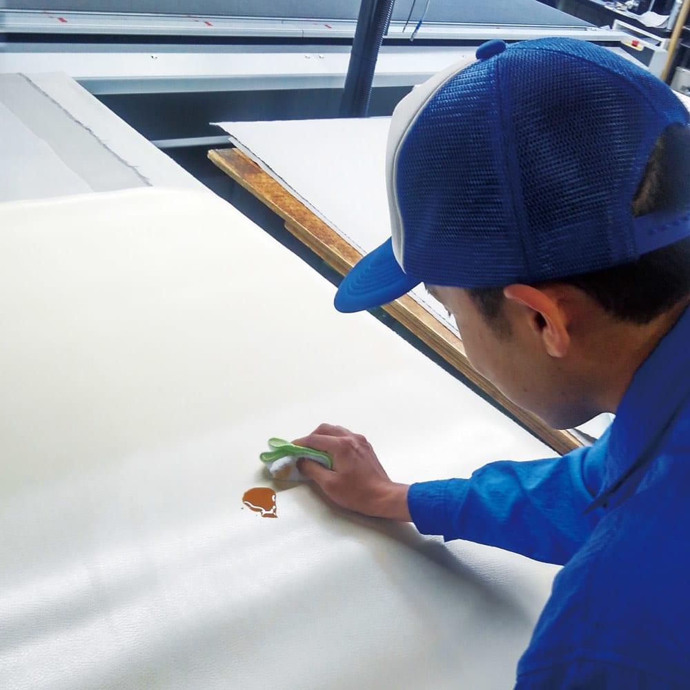 本革調キッチンマット【奥行120cm】 「アキレス」基準の厳しい目で実施する防汚試験もクリア。従来のラグマットとは異なり水分を吸収しにくい素材なので、ソースや調味料などをこぼしてもサッと拭き取ることができ、洗濯も不要です。(アキレス株式会社 フィルム課 山川さん)