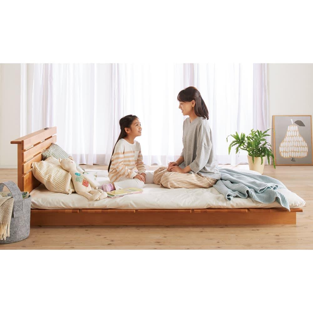 角の丸いアルダー天然木ステージベッドフレーム 棚付き 床に近い低さなので、ベッドが自然と親子のくつろぎの場所に。