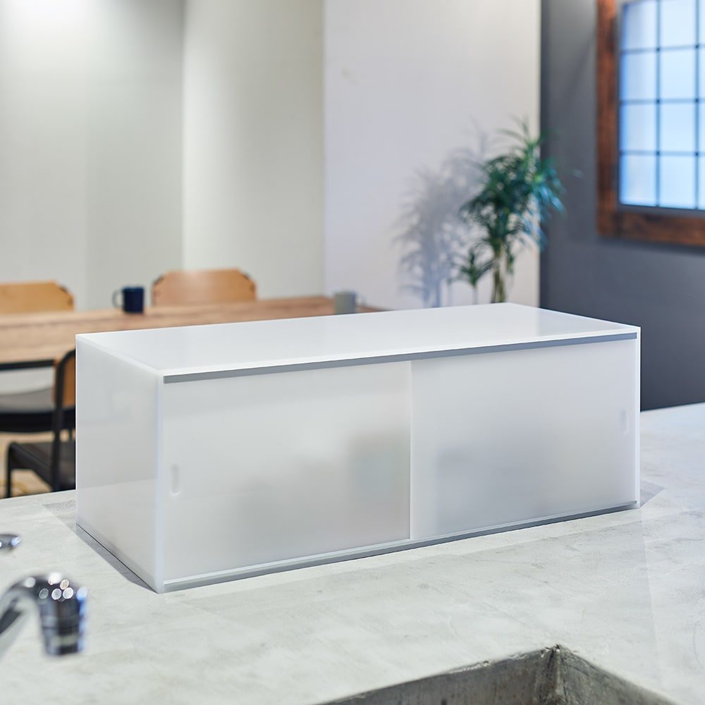 アクリルカウンター上収納庫 幅60cm 奥行25cm 中身がほんのり透けるアクリル製で、洗練された雰囲気を演出。
