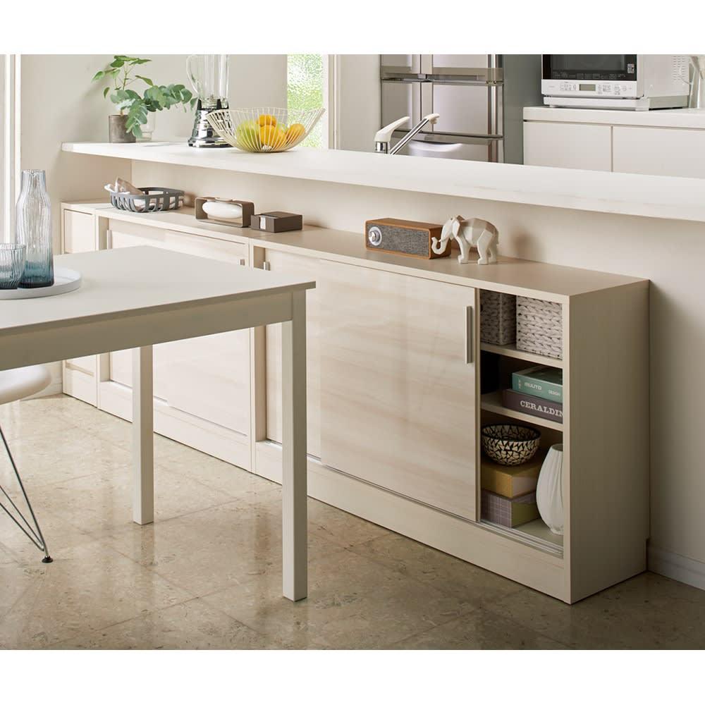 光沢木目が美しい引き戸式カウンター下収納 収納庫幅120cm コーディネート例(ア)ホワイト木目 引き戸だからテーブル近くでも開閉可能。テーブルとつなげて、ちょい置きスペースにも。 ※写真は高さ70cmタイプ