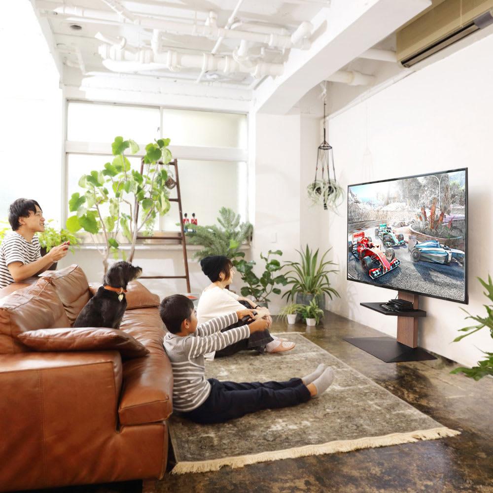 WALL/ウォール 壁寄せテレビスタンド ロータイプ 大 使用イメージ。リビングスペースでテレビを見る時もソファの高さに目線を合わせてテレビを設置できます。