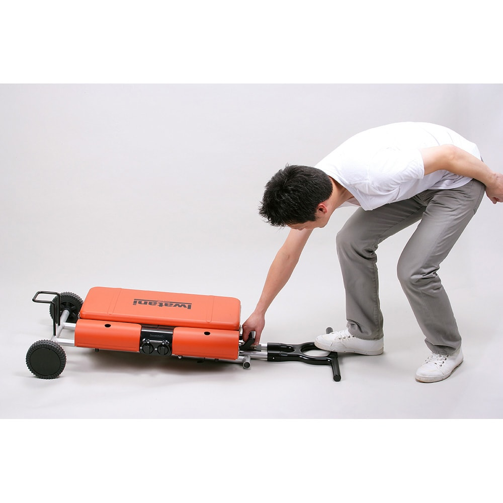 IWATANI カセットガススタンドBBQグリル ラッチ錠を外し、移動用取っ手を足でおさえ、本体取っ手を持ち上げます。