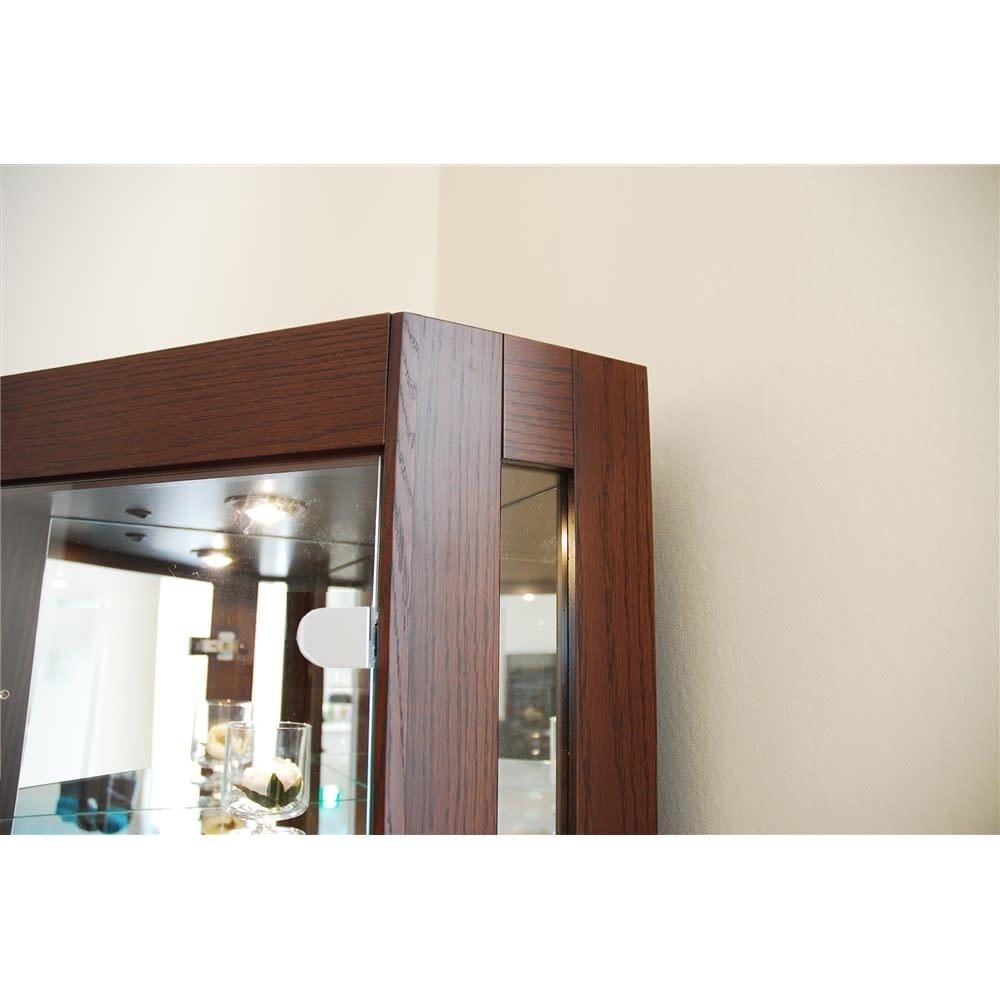 LEDライト付き キュリオコレクションボード コーナータイプ 高さ175cm ブラウン色。扉フレームは高級感あるレーッドオーク天然木を採用。またガラスには5mm厚強化ガラスを採用しました。