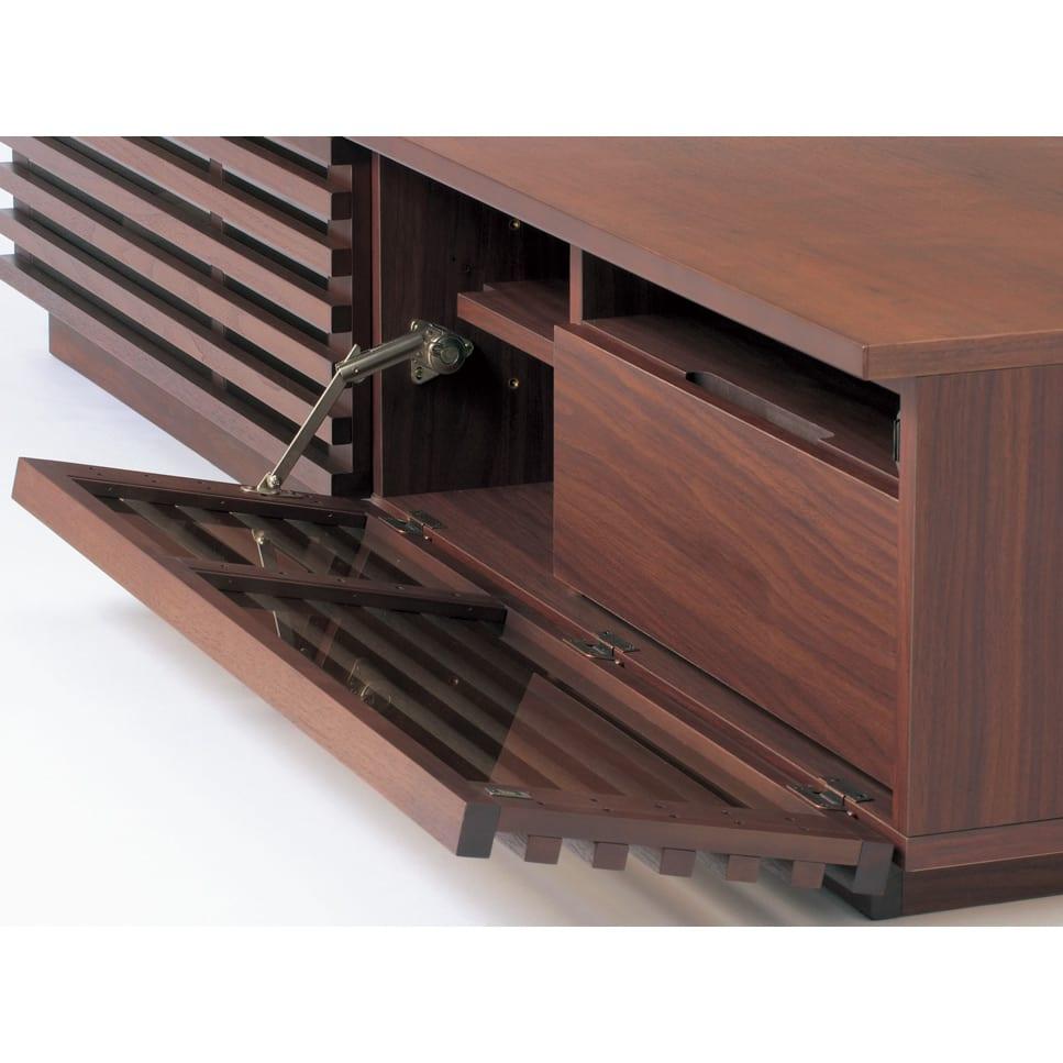 格子デザインシリーズ(ウォルナット) テレビ台 幅180cm 格子のフラップ扉はゆっくり開くソフトダウンステーを採用しました。向かって右フラップ扉を下げると、上段デッキ収納・下段は引き出しです。格子のフラップ扉は閉じたままでもリモコン操作ができます。