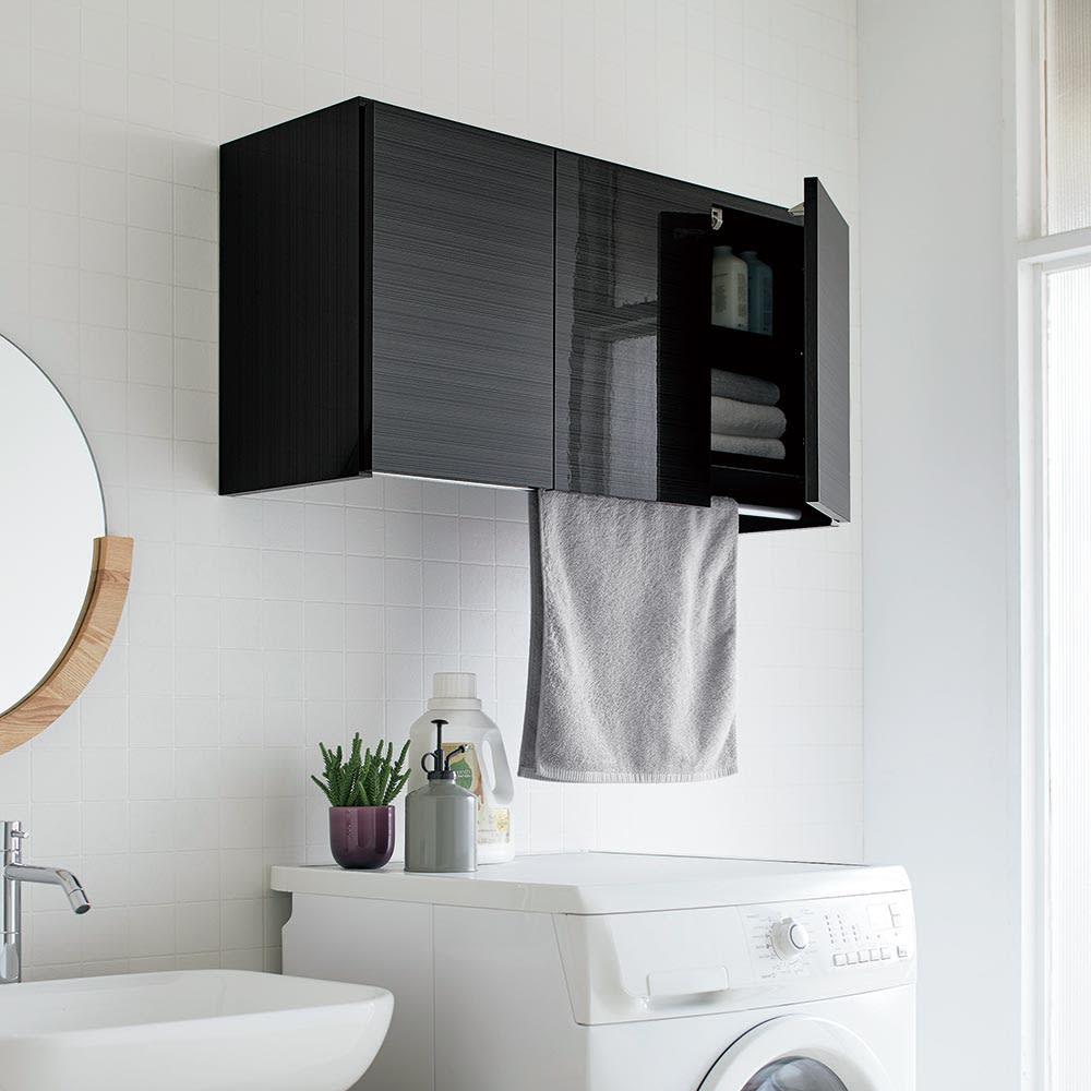 Jerid/ジェリド ハンガーバー付き吊り戸棚 幅89cm 洗濯機上の生活感を品よく隠す艶やかな光沢木目。ブラックの収納庫は、印象をぐっと引き締める効果があります。