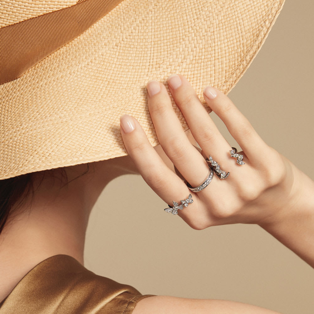 K18WG 0.6ctダイヤ 蝶 ダブルリング コーディネート例 / 二匹の蝶がラインダイヤの先に戯れるダブルリング(人差し指・中指)と、ファンシーカットダイヤが指を挟むフォークリング(薬指)…軽やかだけれど存在感のあるリングをコーディネートしてラグジュアリーな季節感を表現。