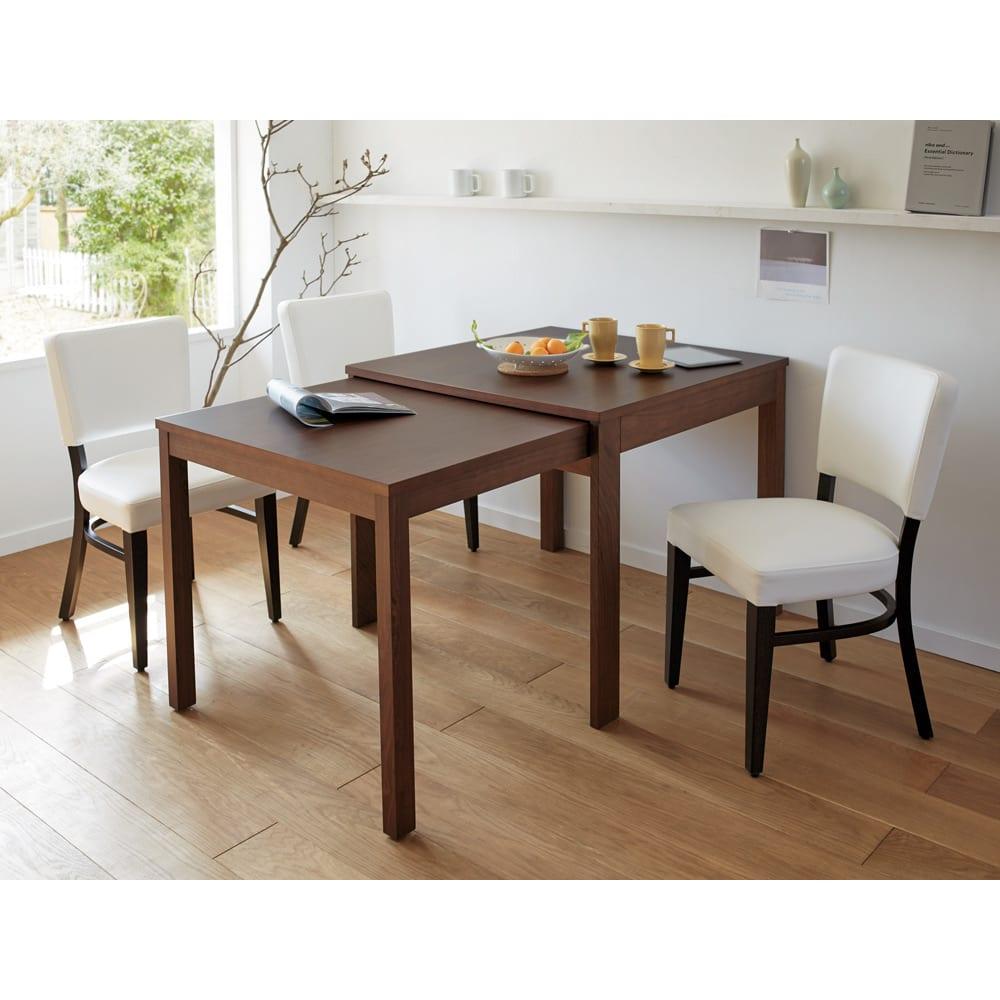 NobuII 伸長式スライディングテーブル ウォルナット材ダイニングテーブル 正方形幅85~143.5cm 伸長時。ホワイトのチェアを合わせて大人でモダンなスタイルのコーディネート。