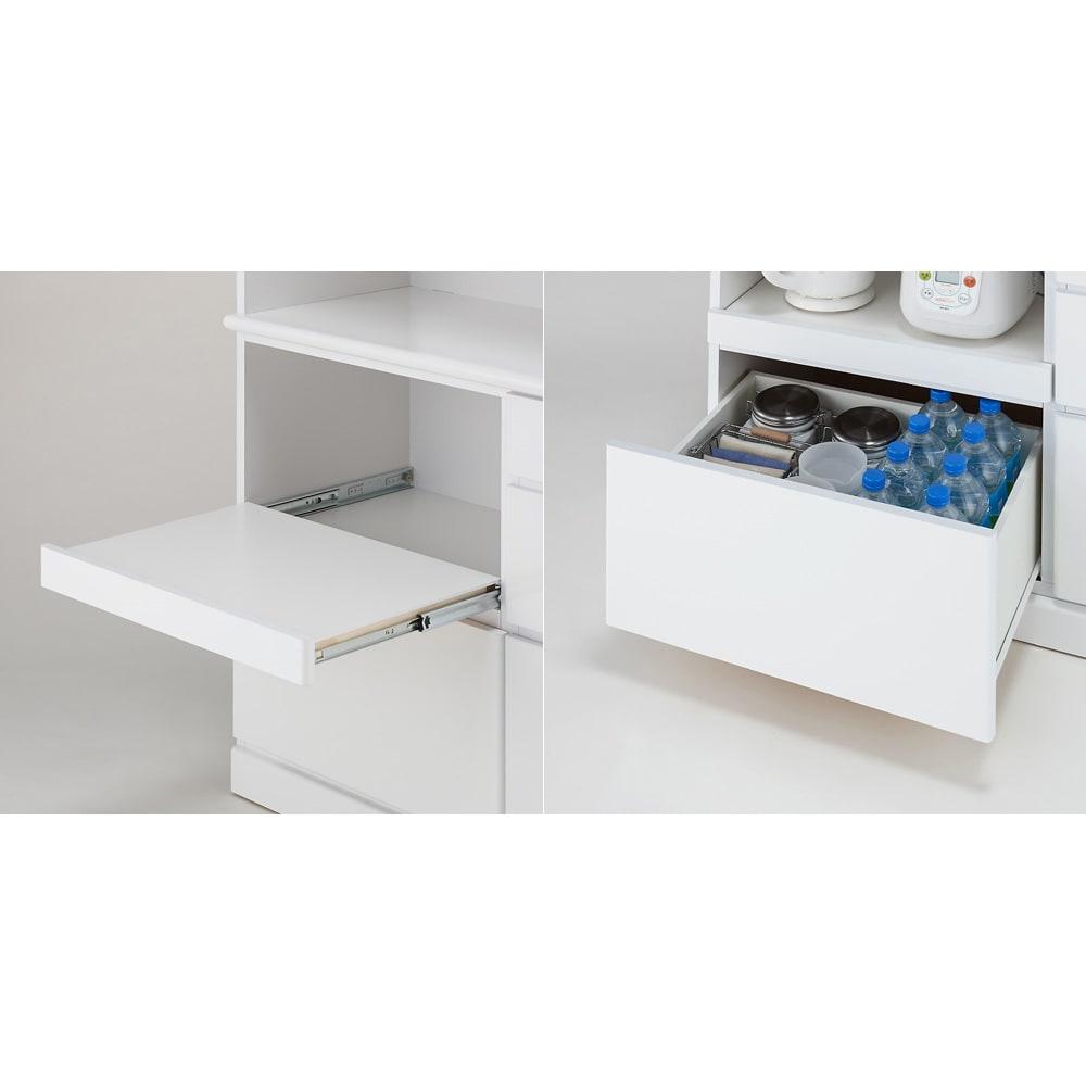 LDK壁面収納(高さ200cm) ダイニングボード ガラス扉 幅86.5cm [写真左]スライドテーブルはフルスライドレールで全開できます。この背面もアルミ化粧板、上面はポリエステル化粧合板を使用しています。[写真右]最下段の深引き出しは大容量。ペットボトルや食品などのストックの収納におすすめです。