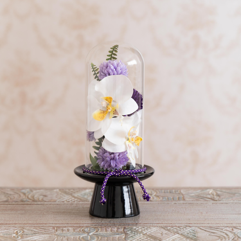 ガラスドームの供花 胡蝶蘭 (ア)パープル系 台座はブラックで小花や組紐がパープルです