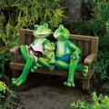 ベンチで読書するカエルの親子