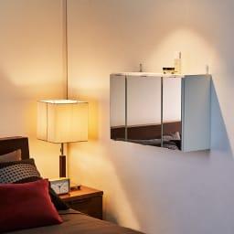 どこでもドレッサースペースにできる 三面鏡付き吊り戸棚 幅89cm 使用イメージ ドレッサーが置けない寝室にも、ベッドに腰掛けたまま使える高さに設置できます。 ※写真は幅59cmタイプです。
