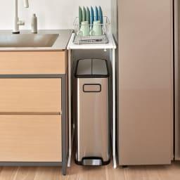 幅が伸縮するキッチン作業台ラック 奥行55cm 幅30cm~50cm 使用イメージ シンクと冷蔵庫の間に設置。天板は水切りカゴの置き場所、下にはゴミ箱も置けます。 ※写真は奥行45cmタイプです。お届けはラックのみです。