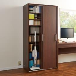 掃除機もしまえる引き戸本棚 ハイタイプ(幅90高さ180cm) 使用イメージ:(イ)ダークブラウン 掃除機などの家電製品を充電しながら収納できます。