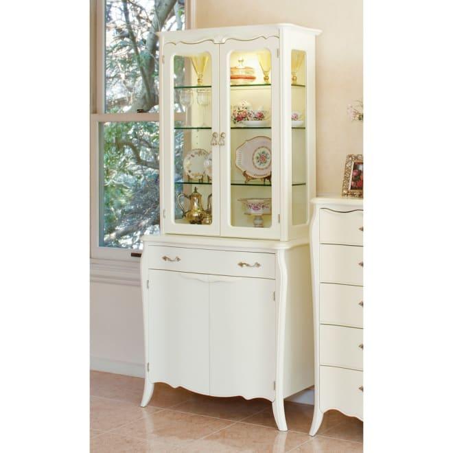 エレガントラインホワイト家具シリーズ 照明付きカップボード ガラスキャビネット式 照明付きでコレクションが映えるガラスキャビネット。扉部分の前板が美しい緩やかな曲線を描いているのが特徴です。