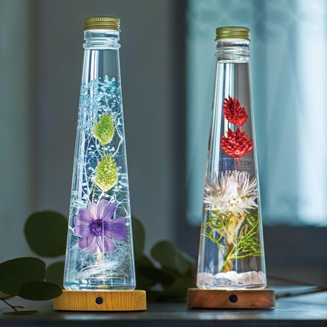 ハーバリウム ボタニックLEDコースター 左から(ウ)ブルー系×ナチュラル、(イ)ピンク系×ブラウン 点灯時 大人っぽいカラーリングのハーバリウムにライトをプラスし、幻想的なインテリアに。コースターからの光をボトルが拡散し、植物の美しさを際立たせます。