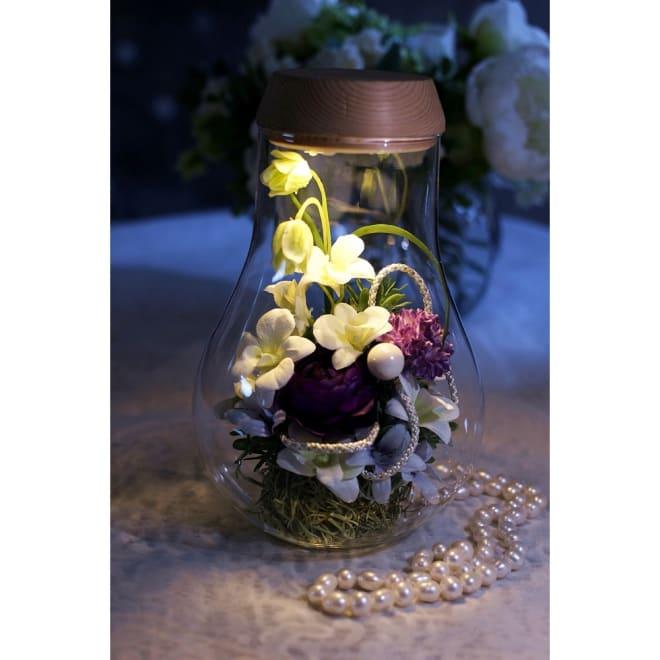 灯る仏花(R) 蘭 蓋に内蔵されたライトをつけるとボトル全体がライトアップされ美しく灯ります。※置く場所の暗さにより点灯時の色味・見え方は異なります。