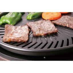 イワタニ マルチスモークレスグリル プレートの中央が盛り上がった形状で、肉から出た脂はプレートにあるミゾから下に落ちて、フチにある穴から下の水皿に落ちる構造です。脂が火にあたらないので煙が出ないのです。